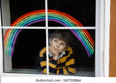 Encantador escolar niño con arco iris pintado con colorido color ventana durante la cuarentena del coronavirus pandémico. La pintura infantil arrecia alrededor del mundo con las palabras Seamos todos buenos.