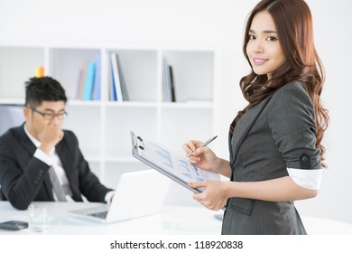 Lovely secretary bringing the annual report to her boss