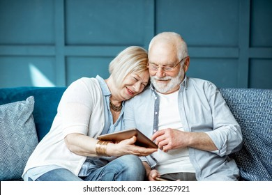 Lovely senior couple dressed casually using digital tablet while sitting together on the comfortable couch at home