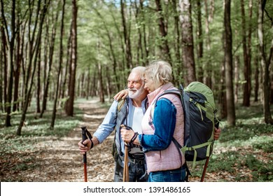 Lovely senior couple hugging in the forest while hiking with backpacks and trekking sticks. Concept of active lifestyle on retirement