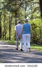 Lovely senior couple out for a walk in the woods on a summer afternoon