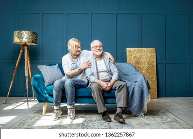 Lovely senior couple sitting together on the couch in the living room at home, wide interior view