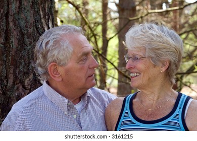 Lovely senior couple together looking at each other outdoors
