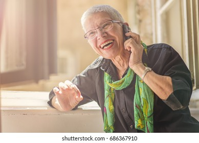 Lovely senior lady having a fun conversation with her friend or