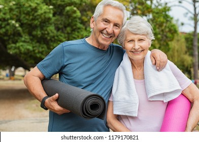Lovely senior man and old woman holding yoga mat for exercising outdoor. Aged husband and wife ready for yoga at park. Active healthy retired couple looking at camera before a postural session.