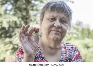 lovely senior woman holding berry fruit