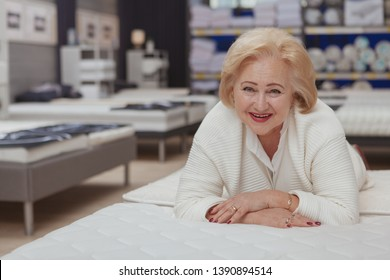 Lovely senior woman laughing to the camera lying on orthopedic mattress at furniture store, copy space. Happy elderly female customer trying beds at furnishings shop