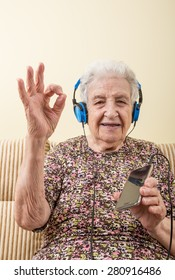 a lovely senior woman listening music (with smart phone / ipod)