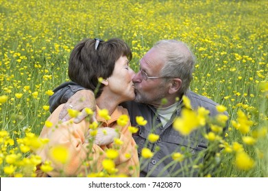 Lovely senoir couple kissing in a green grass field full of buttercups.