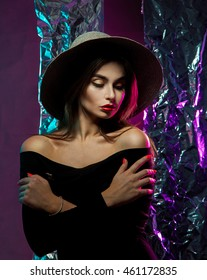 Lovely sensual girl in hat with wide brim and red lips in studio posing and looking down
