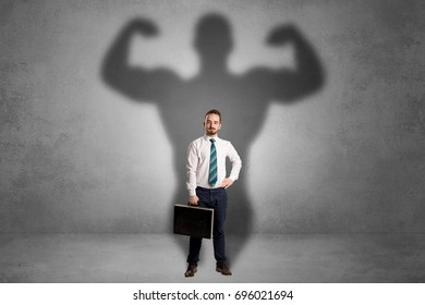 Lovely serious businessman standing with a muscular powerful shadow behind his back