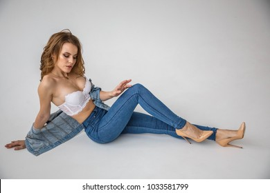 Lovely sexy blonde girl girl in lingerie and jeans posing near window and over white background