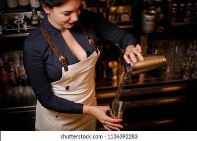 Lovely sexy smiling barmaid with a deep neckline making a fresh summer cocktail in a shaker