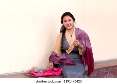 Lovely sikkimese girl with traditional dresses smile to camera while putting the string through the beads, at Do-drul Chorten.Sikkim,India.