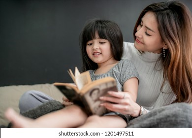 lovely single mom with young girl daughter reading book together on bed family concept