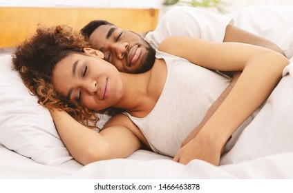 Lovely sleep position. African-american couple sleeping in bed and hugging, close up