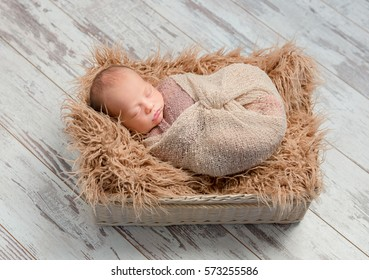 lovely sleeping newborn baby wrapped in basket with fluffy blanket