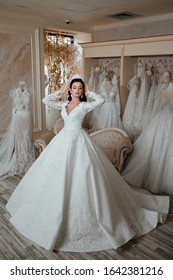 Lovely slim brunette posing in chic wedding dress. Sexy bride. legant cheerful lady in bridal dress standing in wedding salon. Bride with luxurious hair and makeup. Jewelry - Bridal Earrings, Hairsty