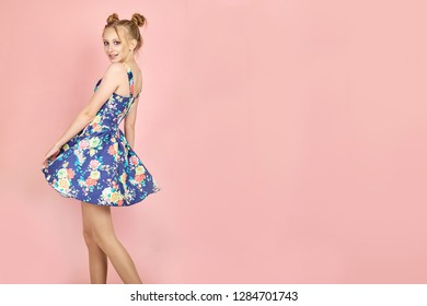 Lovely slim girl posing with sincere smile. female model dancing with hands up on pink background.