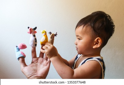 Lovely small man with doll puppets on her hands, smiling and playing