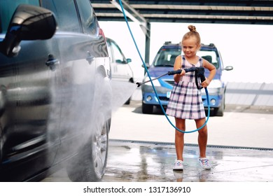 Lovely small preschool girl in summer dress helping to parents use coin-operated self-serve car wash, clean auto exterior holding high-pressure sprayer standing outdoors