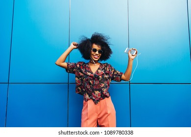 Lovely smiling afro american young woman in sunglasses, dancing while listening to music in headset on her mobile phone. Dressed in colorful blouse and pants. Fun time outdoors.
