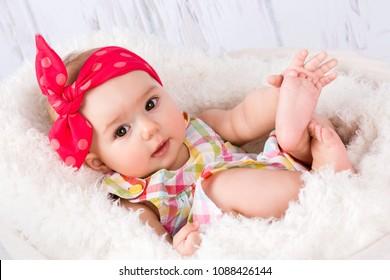Lovely smiling baby girl lying in the basket, studio portrait