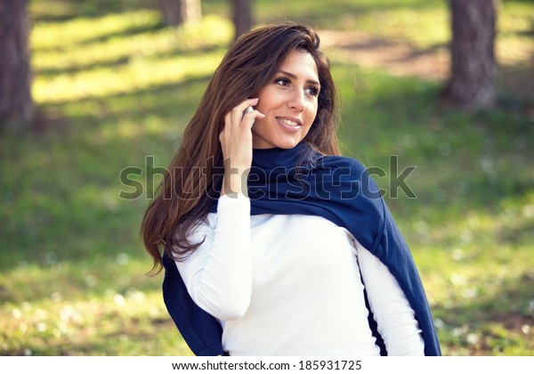 lovely smiling girl talking on mobile phone, against green summer park