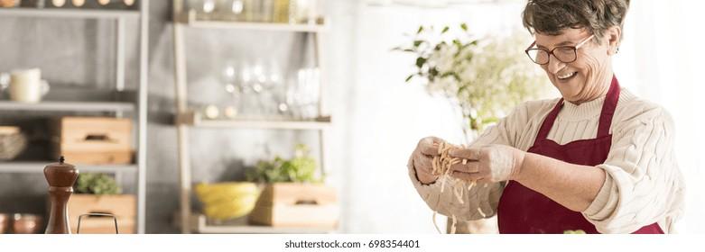 Lovely, smiling grandma preparing tasty, homemade pasta in cozy kitchen