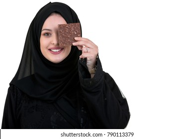 Lovely smiling muslim woman with hijab eating chocolate isolated on white background.