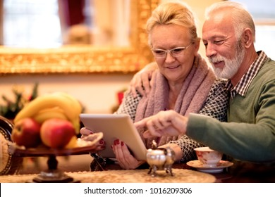 Lovely smiling senior couple having fun while using tablet at nursing home