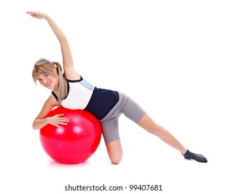 Lovely smiling woman is working out on a red fitness ball