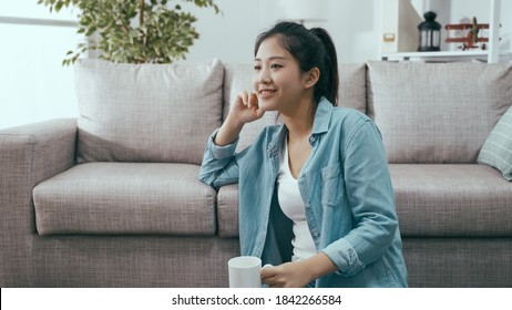 lovely smiling young asian chinese woman sitting by couch is enjoying carefree sunday with cup of hot coffee.