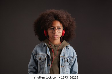 Lovely stylish girl in denim jacket listening to music in red headphones against dark background
