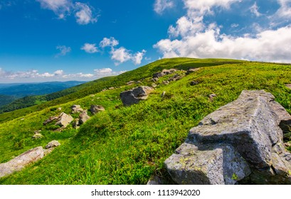 lovely summer landscape. grassy hillside with rocky formations. cloud behind the mountain top. bright and fresh day, good mood. wonderful place for hiking and camping
