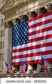 Lovely sun-dappled view of the historic New York Stock Exchange building draped in an American flag.