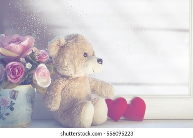Lovely teddy bear and red heart on soft background.