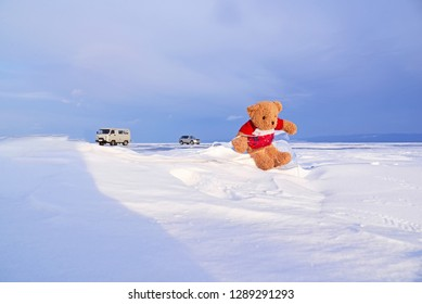 Lovely teddy bear sitting on ice with nature background.Frozen Baikal in Olkhon island, Russia. Concept about happiness on holidays.Butiful landscape in winter season.Dream destination for travellers.