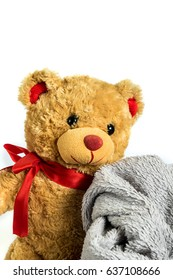 Lovely teddy-bear with a red ribbon wrapped in a grey fluffy blanket isolated on a white background