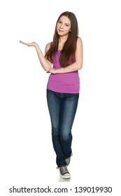 Lovely teen girl in full length standing casually and holding blank copy space at her palm, against white background