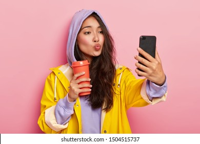 Lovely teenage girl with Asian appearance, keeps lips folded, sends kiss at camera of cellphone, takes selfie, enjoys drink, wears sweatshirt, hood on head, yellow raincoat, has walk after rain