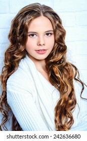 Lovely teenager girl with beautiful long curly hair wears white knitted jersey. Beauty, fashion.