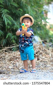 Lovely Thai boy aged 1 year 11 months playing water gun Songkran Festival in Thailand.