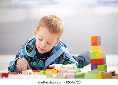 Lovely toddler boy playing with building cubes at home, laying on floor.?