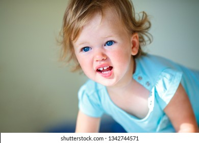 Lovely toddler girl with curly blonde hair indoors. A child showing emotions of sadness and resentment