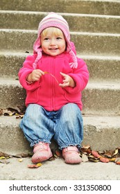 lovely toddler girl sitting on the stairs