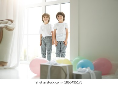 Lovely twins. Two cute latin twin boys, little children in casual wear looking happy, greeting their parents, preparing colorful balloons and giftboxes for them
