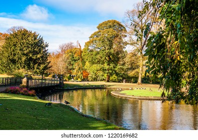 Lovely view of Buxton Park in Autumn, showing the calm pond and beautiful autumnal trees as well as the stone architecture of the town.