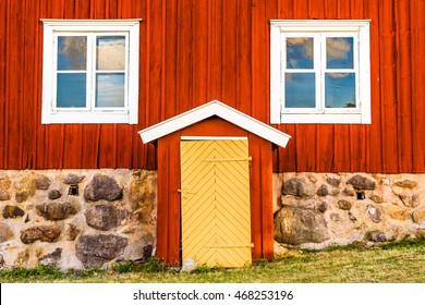 Lovely vintage yellow door on a bright red house with white details.