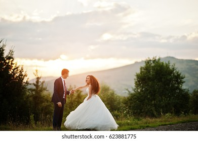 Lovely wedding couple against sunset at Carpathian mountains.